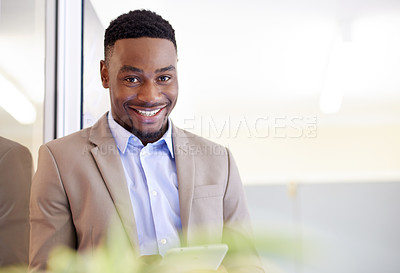 Buy stock photo Portrait of a confident young businessman using a digital tablet in an office