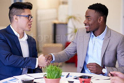 Buy stock photo Shot of two businessmen shaking hands during a meeting in an office
