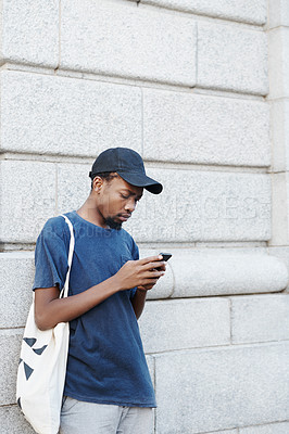 Buy stock photo Shot of a young man using his cellphone while out in the city