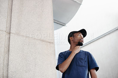 Buy stock photo Cropped shot of a handsome young man posing outside
