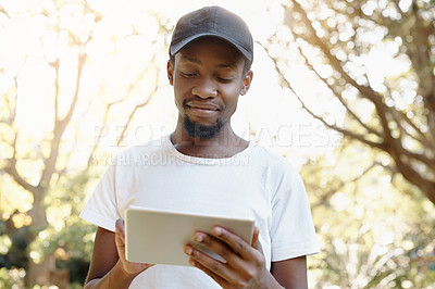 Buy stock photo Cropped shot of a handsome young man using his tablet outdoors