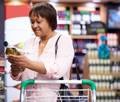 Buy stock photo Shot of a mature woman reading the label of an olive oil bottle in a grocery store