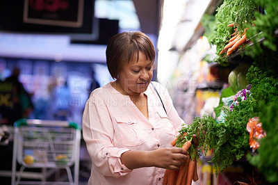 Buy stock photo Shot of a mature woman shopping for healthy food in a grocery store
