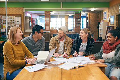Buy stock photo Shot of a cheerful young group of students studying together while having a discussion inside of a library