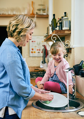 Buy stock photo Shot of a cheerful young mother and her young little daughter washing dishes together at home