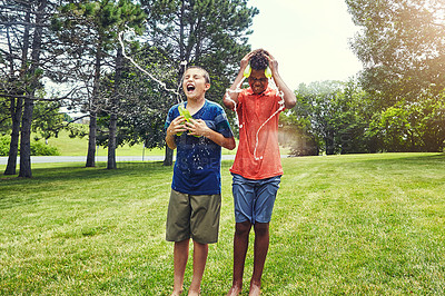 Buy stock photo Shot of adorable young boys playing with water balloons outdoors