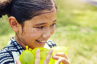 Buy stock photo Shot of an adorable little girl playing water balloons outdoors