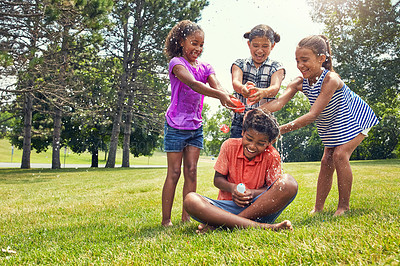 Buy stock photo Shot of adorable children playing with water balloons outdoors