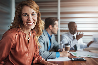 Buy stock photo Portrait of a confident businesswoman sitting in an office with her colleagues in the background