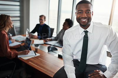 Buy stock photo Portrait of a confident businessman sitting in an office with his colleagues in the background