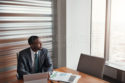 Buy stock photo High angle shot of a handsome businessman looking thoughtful while working in his corporate office