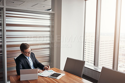Buy stock photo High angle shot of a handsome businessman working in his corporate office