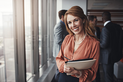 Buy stock photo Portrait of a professional businesswoman standing in an office with colleagues in the background