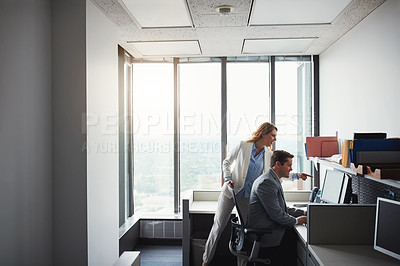 Buy stock photo Cropped shot of woman standing behind a man as he work on his computer