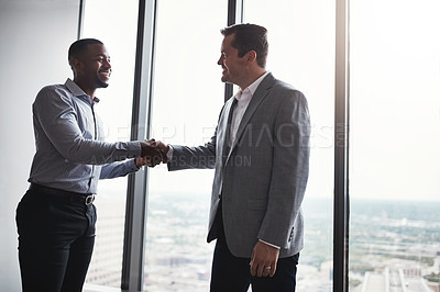 Buy stock photo Cropped shot of two corporate businessmen shaking hands during a meeting in the boardroom