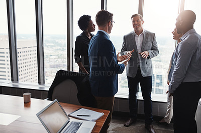 Buy stock photo High angle shot of a group of corporate businesspeople meeting in their boardroom