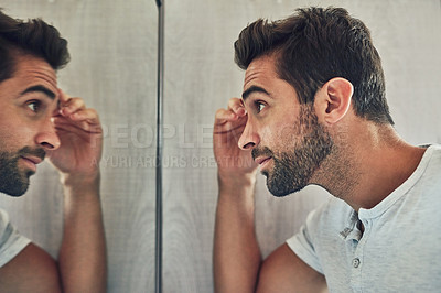 Buy stock photo Shot of a confident young man looking at himself closely in the mirror at home during the day