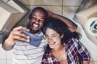 Buy stock photo High angle shot of a young couple taking a selfie in their new home