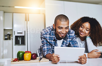 Buy stock photo Shot of a young couple using a tablet together at home