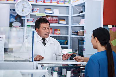 Buy stock photo Shot of a male pharmacist helping a female customer in a pharmacy