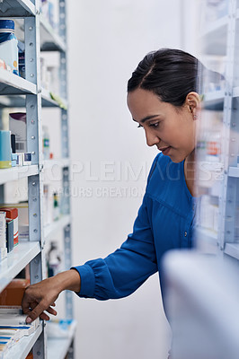 Buy stock photo Shot of a young woman shopping at a pharmacy