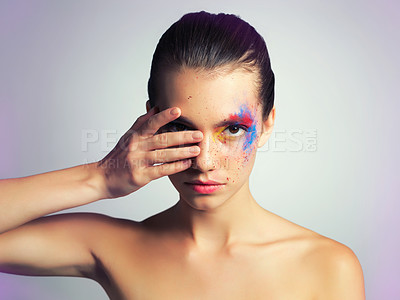 Buy stock photo Studio shot of an attractive young woman posing with her face brightly painted