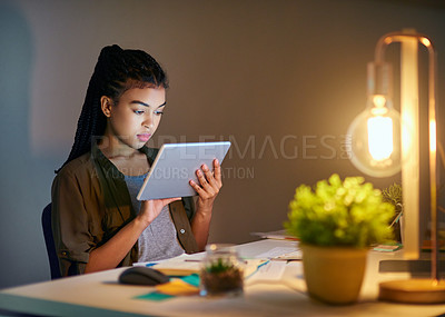 Buy stock photo Shot of a young businesswoman using a tablet at the office