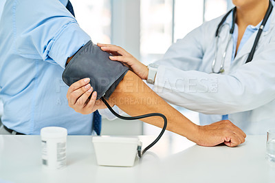 Buy stock photo Closeup shot of a doctor checking a patient's blood pressure in a hospital