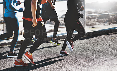 Buy stock photo Cropped shot of a group of unrecognizable people out for a run