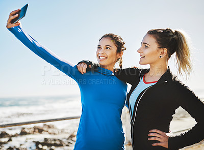 Buy stock photo Cropped shot of two friends taking a selfie while out for a run on the promenade