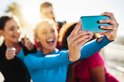 Buy stock photo Cropped shot of a fitness group taking a selfie while out for a run on the promenade