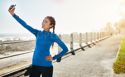 Buy stock photo Cropped shot of a woman taking a selfie while out for a run on the promenade
