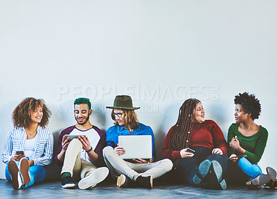 Buy stock photo Studio shot of a group of young people sitting on the floor and using wireless technology