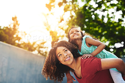 Buy stock photo Shot of a happy little girl and her mother enjoying a piggyback ride in their backyard