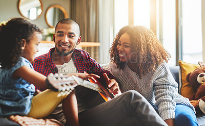 Buy stock photo Shot of an adorable little girl and her parents playing a guitar together on the sofa at home