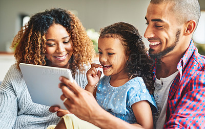 Buy stock photo Shot of an adorable little girl and her parents using a digital tablet together on the sofa at home
