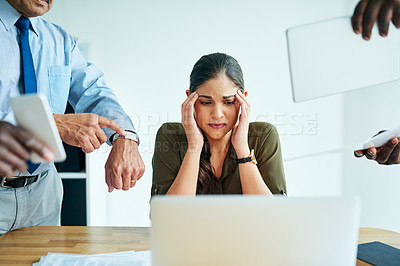 Buy stock photo Shot of a stressed out businesswoman surrounded by colleagues needing help in an office