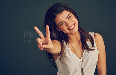 Buy stock photo Studio shot of a cheerful young woman showing the peace sign while standing against a dark background