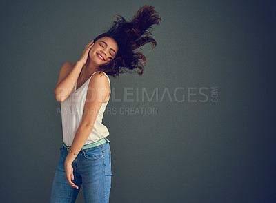 Buy stock photo Studio shot of a carefree young woman holding her face while her hair gets blown by wind against a dark background