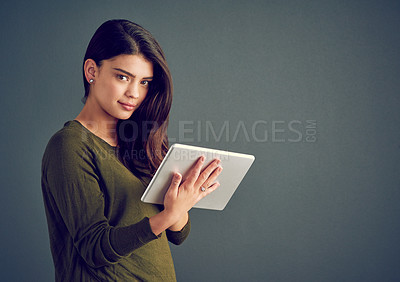 Buy stock photo Studio shot of an confident young woman holding a digital tablet while standing against a dark background
