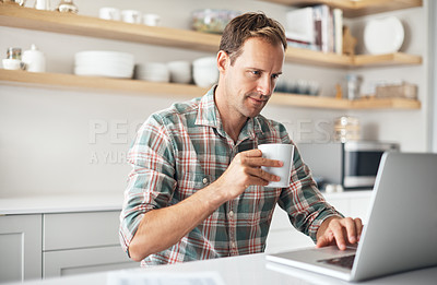 Buy stock photo Shot of a mature man drinking coffee while using a laptop at home