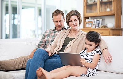 Buy stock photo Shot of a little girl and her parents using a digital tablet together at home