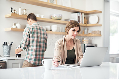 Buy stock photo Shot of a woman using a laptop with her husband in the background at home