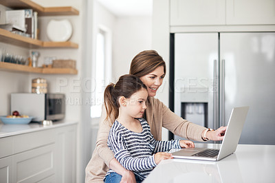 Buy stock photo Shot of a mother and her little daughter using a laptop at home