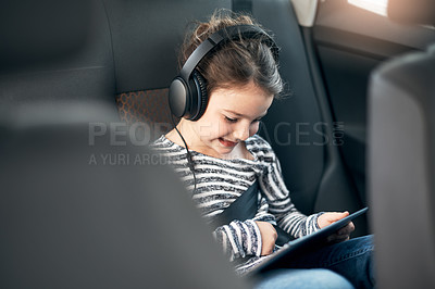 Buy stock photo Shot of an adorable little girl wearing headphones while using a digital tablet in the backseat of a car