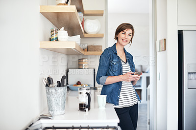 Buy stock photo Cropped portrait of an attractive young woman using her cellphone while standing in the kitchen at home