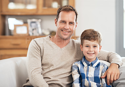 Buy stock photo Cropped portrait of a handsome young man and his son sitting on the sofa at home
