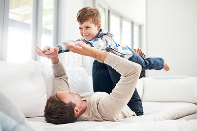 Buy stock photo Full length shot of a handsome young man playing with his son on the sofa at home