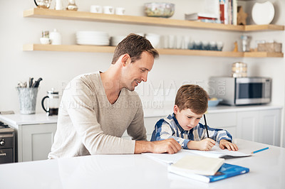 Buy stock photo Cropped shot of a handsome young man helping his son with his homework while sitting in the kitchen at home