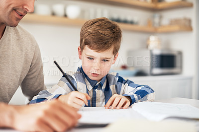 Buy stock photo Cropped shot of an adorable little boy doing his homework while sitting in the kitchen with his father